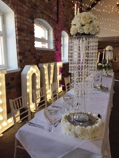 Chandelier tower centrepiece with rose top. #piecesandposies