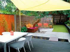 An urban backyard is transformed into a living family sanctuary that features an area for dining, lounging and playing.