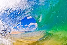 A surfer's perspective looking out of a crystal clear tube. The glassy & light wind conditions make the wave transparent and glass-like, showing the sand on the ocean floor, in Oahu, Hawaii.