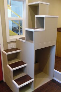 A custom storage staircase with room for washer/dryer combo leads up to the main bedroom loft.
