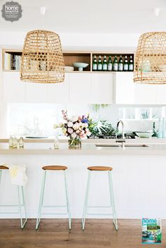 Bright kitchen with mint colored stools and rattan  pendant lights