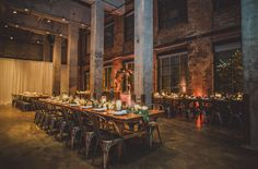 Industrial wedding reception - long farm tables with flowering garlands and the glow of clustered candles, creating such a cozy dinner party feel