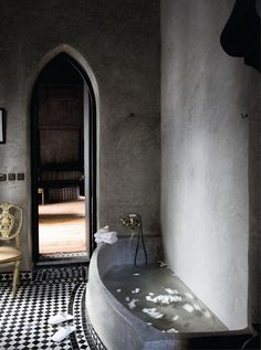 doorway gothic archway for bathrooms and storage room. black and white tiles. natural concrete finish. gold accents.