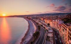 The Walkway of the English - Warm evening sunlight highlights the beachfront buildings of Nice and the Promenade des Anglais. Nice came to the attention of the English upper classes in the second half of the 18th century, when an increasing number of aristocratic families took to spending their winter there. The city's main seaside promenade, the Promenade des Anglais ('the Walkway of the English') owes its name to the earliest visitors to the resort.