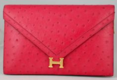 This Hermes Rare Vintage Two Way Lydie Clutch is done in Bright Pink Ostrich.  The hardware is gold plated.  The single flap with H snap closure secures the pink Leather interior.  The removable  Ostrich shoulder strap has a handle drop of 15 inches. - goalsBox™