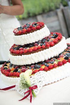 Torta nuziale a tre piani con frutta fresca e panna per un matrimonio rustico