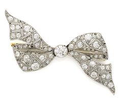 A belle époque diamond bow brooch, circa 1915 composed of old European-cut diamonds accented by rose-cut diamonds; estimated total diamond weight: 2.20 carats; mounted in platinum-topped eighteen karat white gold
