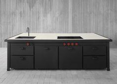 """Cucina componibile ad isola, in metallo nero. Piano in cemento. Il piano è attrezzato con lavello, piano cottura ad induzione e """"coup de feu""""."""