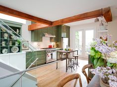 The exposed beams and natural wood kitchen island countertop and dining table in this kitchen bring a rustic touch to the space. The green cabinets bring about a natural feel, while the French doors let in lots of natural light, as seen on HGTV's hit show Love It or List It.