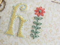 "The ""I"" is a cute flower made almost entirely with lazy daisy stitches. Instructions on how to draw and follow the design using dots."