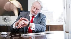 Mature businessman looking at watch
