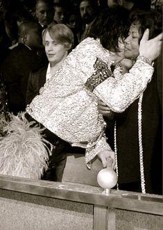 Michael Jackson gives mom a kiss. Macaulay Culkin is behind them.