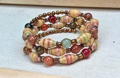 Wrap around memory wire bracelet handmade from yellow, red & green floral patterned paper complemented with colorful agates, gold seed beads, copper