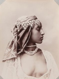 A gorgeous woman in Algiers, the capital of Algeria, in the 1900s. The coins on her head dress are so lovely. I love how statuesque she looks, how regal.