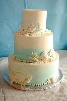 Beach wedding cake with seashells and daisies