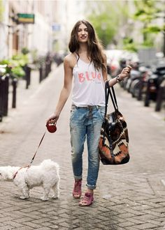 tank top, jeans, big bag and a dog.