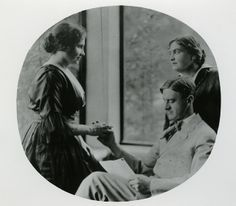 HELEN KELLER conversing with John Macy, who married ANNE SULLIVAN in 1905.  John Macy is sitting in a chair and fingerspelling into Kellers' ...