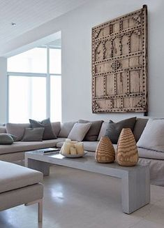 Antique wooden door in a contemporary living room. Love the wooden vessels on the coffee table.