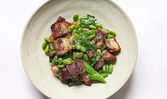 Pork belly chunks and edamame beans on a round dish