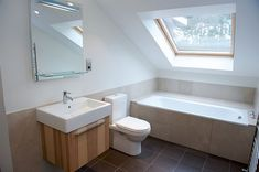 A light, relaxing family bathroom with a skylight window above the bath.