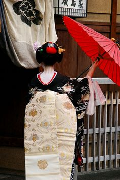 red umbrella with black kimono and ivory + gold intertwined obi