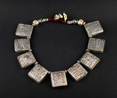 An old Amazigh (Berber) amulet necklace from Taroudant, Morocco with nine small silver amulet boxes with brass backings engraved with a floral design and enamel much of which has rubbed off'.