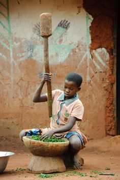 A girl pounds #cassava (manioc) leaves to prepare them for cooking a staple dish in northwest #Congo. (Photo: ©2011 Jon Warren/World Vision)