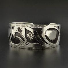 Diese einzigartige Native American First Nations-Armband misst 1 x 6 und passt eine Handgelenk zwischen 6 1/4- 6 3/4 im Umfang. Es zeigt einen Adler als Symbol des Stolzes und der Freundschaft in den meisten einheimischen Gemeinden im Pazifischen Nordwesten.    Es wurde erstellt mitschwarz-weiß Methode einhergehende Gravieren und schneiden-aus einem Stück Sterlingsilber und dann mühsam Löten auf ein zweites Gepäckstück 925er Silber. Es dauerte der Künstler zwei Wochen dieser erstaunlichen…