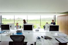 Modern office in a rural setting showing the glass facade and four employees consulting