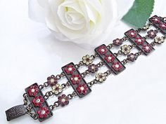 $85  Unique statement bracelet with hundreds of Swarovski shimmering crystals in red, purple and very light yellow. Feel instantly elegant and regal when you wear this bracelet!  www.rachelflamdesign.etsy.com