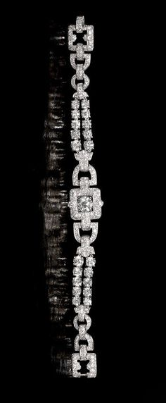 A diamond bracelet, by Cartier, circa 1935 Designed as a series of buckle-shaped links, pavé-set with old brilliant and single-cut diamonds, connected by highly articulated courses of old brilliant-cut diamonds, the principal old brilliant-cut diamond to the centre, mounted in platinum, principal diamond approximately 1.75 carats, remaining diamonds 12.80 carats total, signed Cartier, length 18.4cm