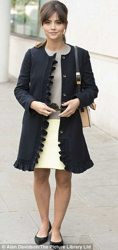 Black collarless, feather trimmed coat + grey top and white skirt + pointed black pumps
