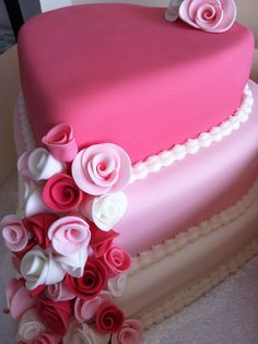Three tiered pink heart shaped wedding cake adorned with handmade sugar roses