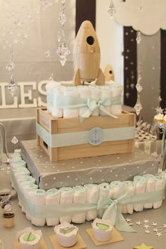 I just adore this decorative space shuttle diaper cake. The square boxes give it a neat and tidy look. This can go on the gift table near entrance. For the perfect ribbon, look here: http://www.minted.com/product/ribbons/MIN-00S-RBB/mint-shimmer?ccId=147233&org=photo