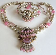 This is a stunningly beautiful vintage necklace and bracelet set by designer Miriam Haskell. The two strand pendant necklace and coil style bracelet are exquisitely fashioned with strands crafted from a beautiful assortment of lustrous faux baroque pearls, glistening translucent pink glass beads and smooth pink poured glass beads. There are shiny gold tone spacer beads in between the lovely pink beads and glossy pearls, some of which are gilt filigree capped. Each of the necklace and…