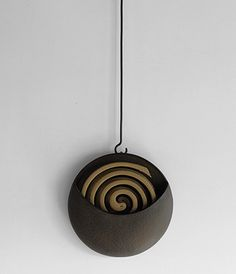 "Designed by Sゝゝ the hanging coil burner is produced at the Morihisa Suzuki Workshop in Morioka Iwate, the hometown of ""Nanbu Iron"". The Morihisa Suzuki Workshop has been producing iron products since 1625 and their traditional metal-casting method gives there products a distinctive texture."