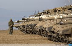 An Israeli soldier walks next to Merkava tanks stationed in a deployment training area in the Israeli-annexed Golan Heights near the border with Syria on August 28, 2013