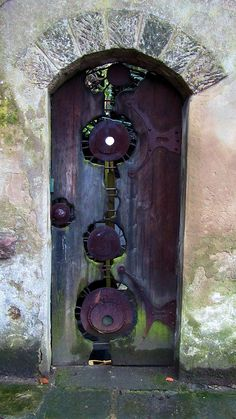 Quirky circles of metalwork on this purple door in Wirksworth, England.