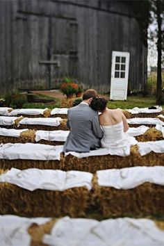 Exterior Barn Wedding Décor - blanket covered hay bales lend a rustic charm for ceremony seating