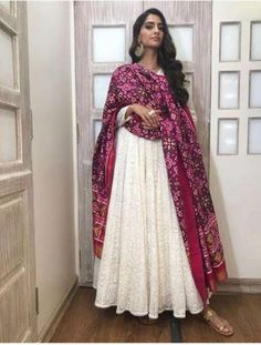 We came across a photo of Sonam Kapoor on social media in which she looks stunning in a white outfit with intricate embroidery. Sonam has paired it with a magenta colored dupatta; soft curls and statement earrings completed her look. Indian Gowns Dresses, Indian Fashion Dresses, Dress Indian Style, Casual Indian Fashion, India Fashion, Indian Wedding Outfits, Pakistani Outfits, Indian Outfits, Indian Attire