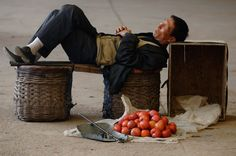 exhausted:  A vendor selling Chinese watermelons takes a nap at a wholesale market in Huaibei, China.