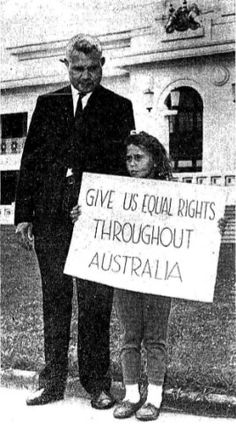 J Hassen and daughter protesting in fron of Parliament House. Their sign reads: 'Give us equal rights throughout Australia'.