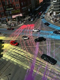 Guerilla Paint Action. A group of cyclists dumped 13 gallons of paint on the road at Berlin, creating a series of colourful lines as cars drove through.  Bikers had poured paint from big boxes in front of cars that waited for green lights. So the cars and their wheels, if the driver wanted it or not, became the brush tool for this guerilla public art piece.The creators of the project posted signs on post nearby explaining that the paint wasn't harmful and would simply wash off with water.
