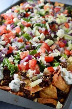 Fully loaded Greek Gyro Nachos with pita chips, tzatziki sauce, tomatoes, onions, cucumbers, olives and a whole lotta feta.