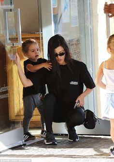 Adorable: Reign grabbed his mom's shoulders as the family made their way out of the studio