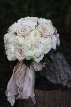 This lush bouquet features a rich ribbon treatment that we love using. The flowers used to create the bouquet include white cabbage roses, white polo roses, blush pink roses, white ranunculus, white stock, white hydrangea,  and green gardenia foliage.