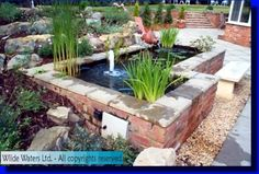 Here 39 s a rectangular raised stacked stone above ground for Brick fish pond