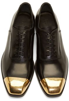 Black Leather Toe Cap Oxfords by Alexander McQueen. Buffed leather oxfords in black. Gold-tone metal cap at square toe with aged finish throughout. Tonal lace-up closure. Leather sole. Tonal stitching. Upper: leather. Sole: leather. Made in Italy. http://www.zocko.com/z/JEwYq