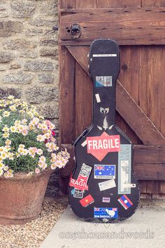 Guitar case with stickers leans on wooden door at Dorset Barn Wedding. Photography by one thousand words wedding photographers