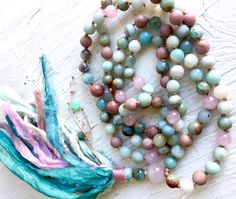 Sweet combination of pastel favorite gemstone beads. Rose Quartz, Amazonite, African Opal Rhodonite and Aquamarine. This mala is finished with a matching silk sari tassel with four beads hanging from the beaded thread. This design adds interest to the mala as well as making it